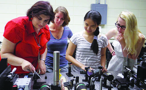 Associate Professor Madalina Furis, director of materials science, observes gear with with Alice Perrin from the College of William and Mary, Kim Hua and UVM senior Victoria Ainsworth. PHOTO COURTESY OF MADALINA FURIS