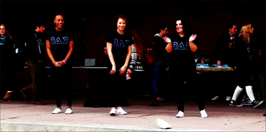 (Left to right) Fraternity members sophomore Sha'Kylah Morris, junior Sheila Cruz and graduate Lynn Wales perform an initiation ritual in front of the Bailey/Howe Library Nov. 19. photo courtesy of Theta Sigma Delta at UVM