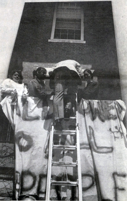 President George Davis climbs a ladder to get into his own office in order to negotiate with the student protesters occupying the building April 23, 1991.