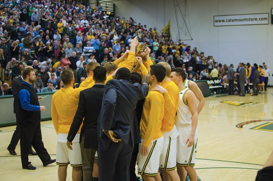 Men's basketball players gather together
