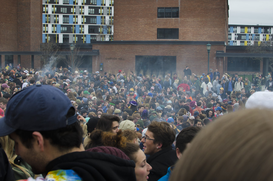 OLIVER POMAZI | The Vermont Cynic UVM students gather on the Redstone Green April 20 to participate in 4/20 activities as UVM Police look on.