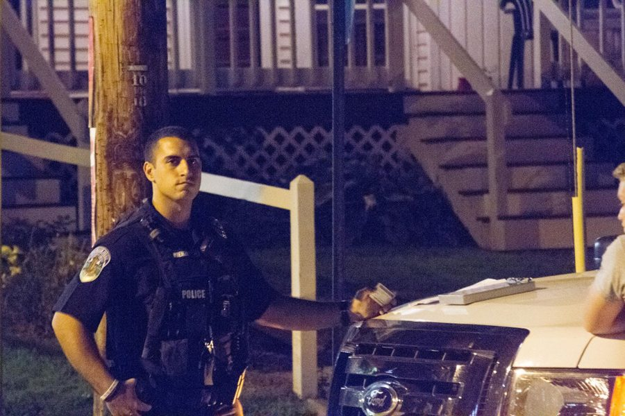 Burlington police officer on duty standing by his car interacting with a student Sept. 5 on Buell St.