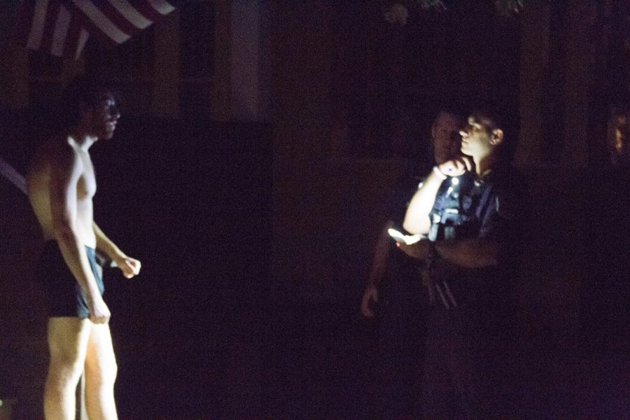 A Burlington police officer shines his light on a student resident of Buell St. Sept. 5.