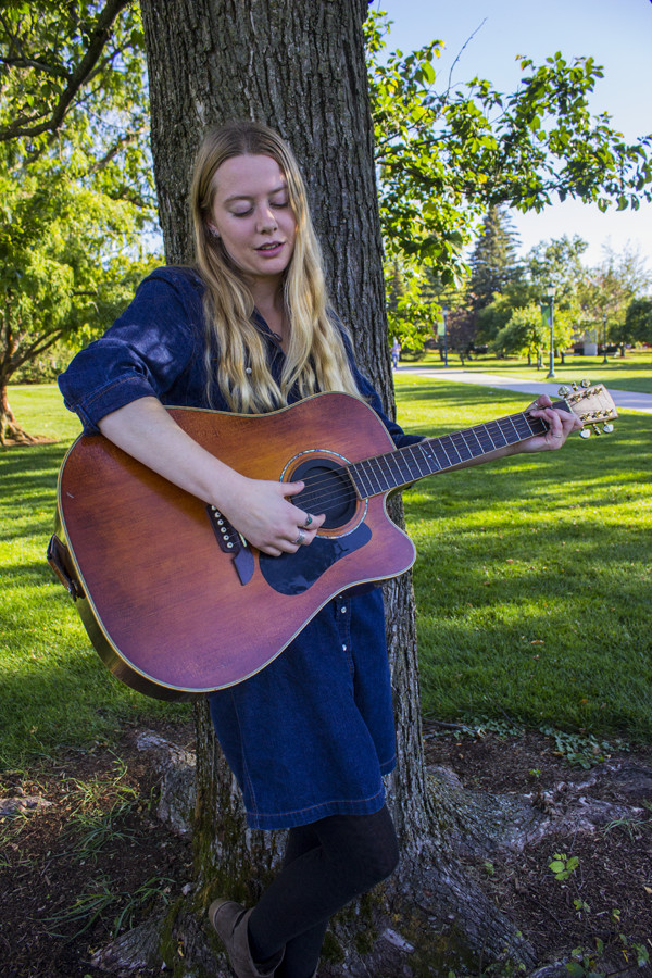 Senior Kristi Blow practices guitar on the Waterman green Oct. 18. Blow, a singer-songwriter, will be performing at Radio Bean Nov. 5.