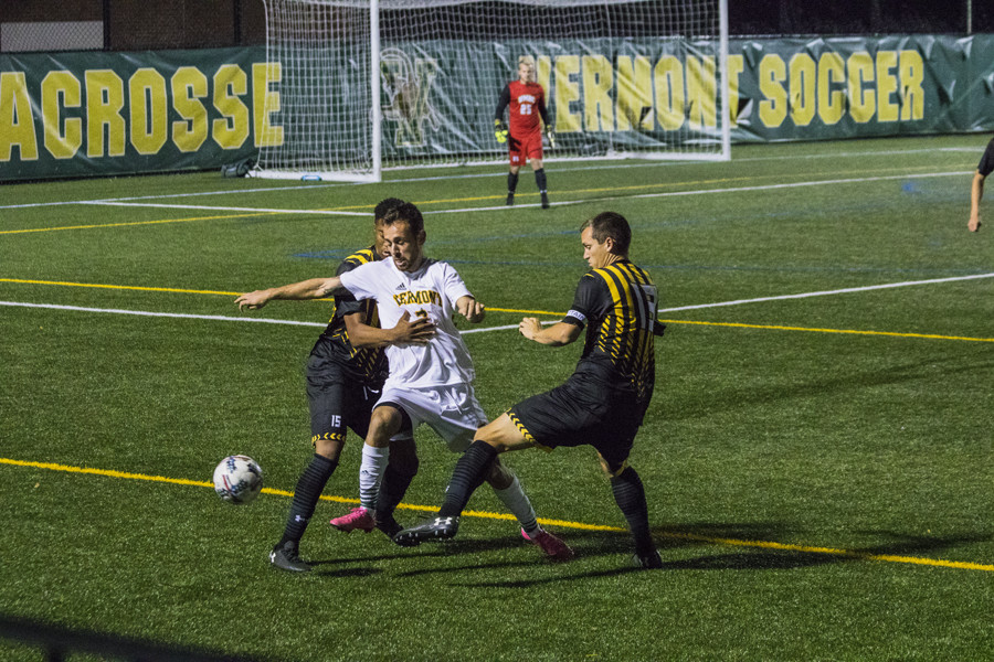 Junior forward Justin Freitas dribbles between two UMBC players Oct. 21. Freitas scored twice in the game, carrying the Catamounts past the Retrievers 3-1.