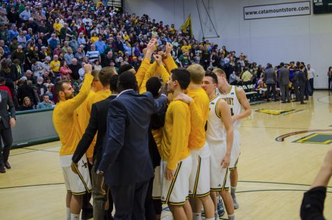 The men's basketball team huddles together before a game Feb. 2. The Catamounts have high expectations for this year after finishing last season with a perfect conference record.