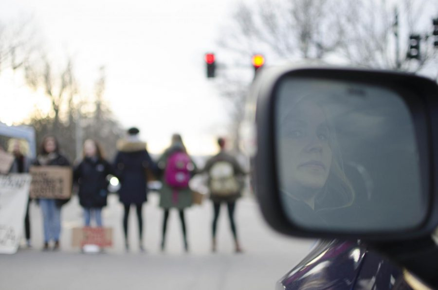 A+woman+in+traffic+looks+on+to+the+line+of+protestors+blocking+Main+Street.
