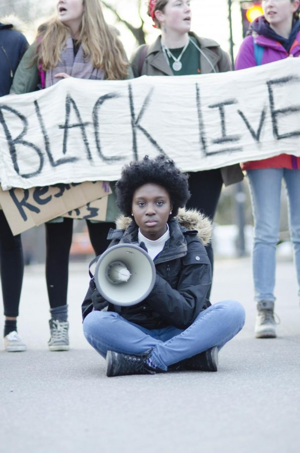 Sophomore and NoNames leader Harmony Edosomwan sits in front of protestors.