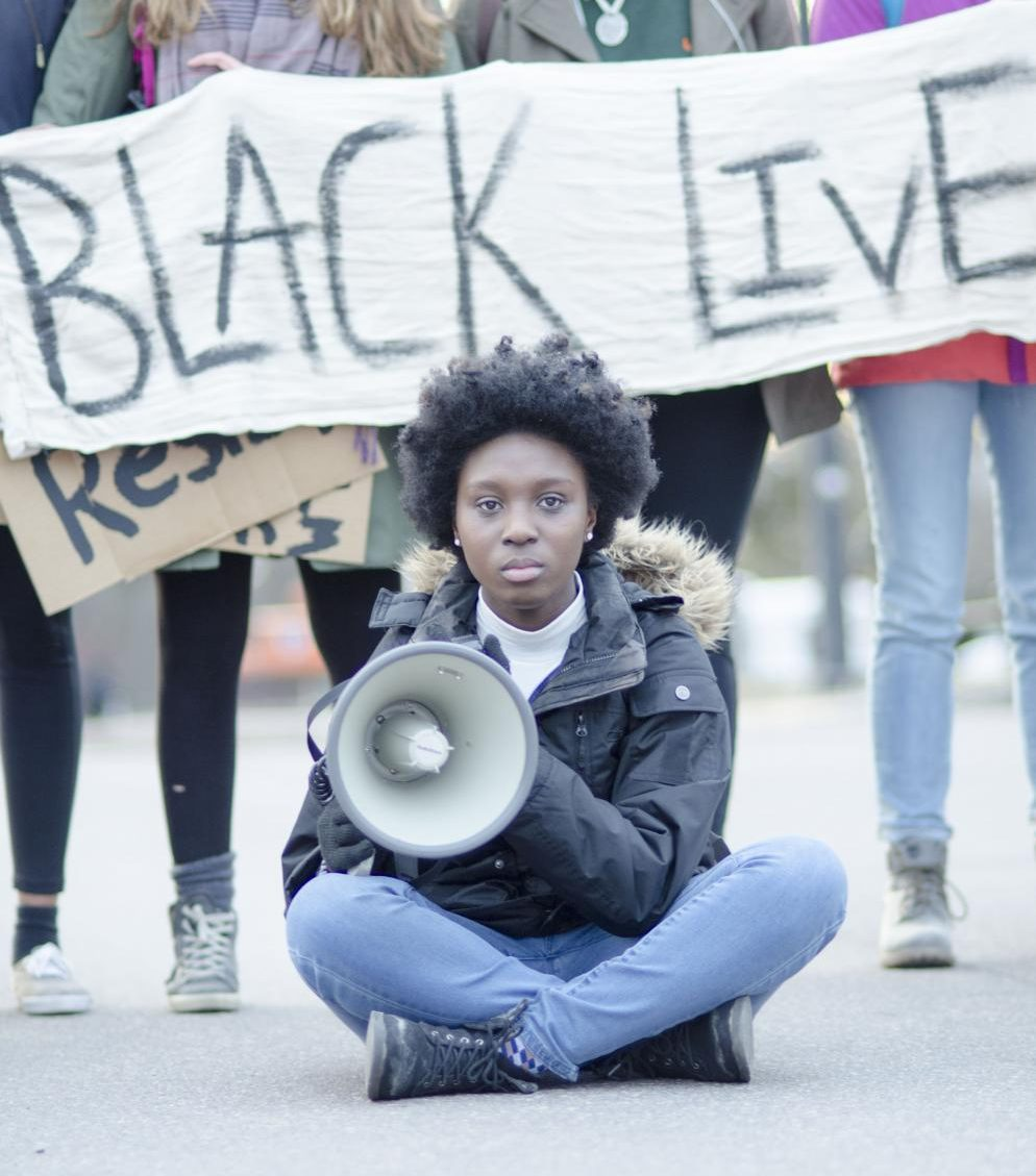 Sophomore BSU President Harmony Edosomwan sits in the middle of Main Street during the protest.