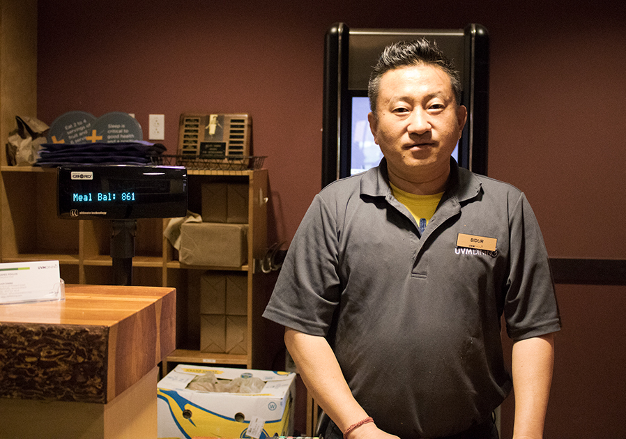 Bidur Rai stands at the front desk of Simpson Dining on Redstone Campus