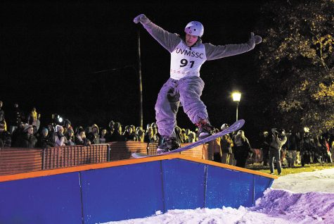 Senior Diego Travino grinds a rail in an all gray onesie at the Dawn of the Shred X: the Human SENDipiede rail jam, hosted by the UVM Ski and Snowboard Club Oct. 25.