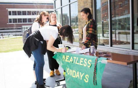 Sophomore Margaret Thomson tables outside of Central Campus Dining Hall for Meatless Mondays April 25, 2017. Green Mountain Veggies is starting Meatless Mondays at UVM dining halls on a small scale Nov. 12 and 26 as well as Dec. 3 and 10.