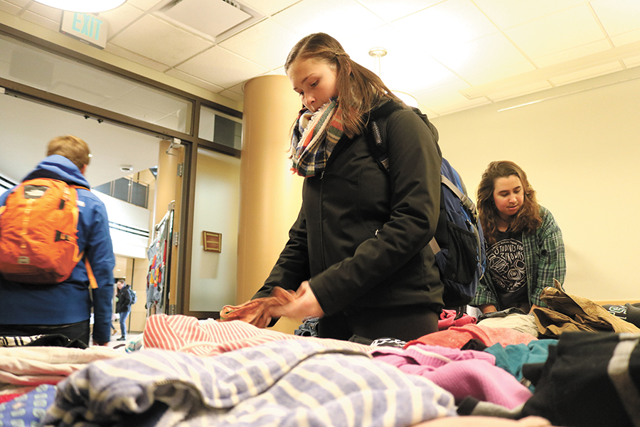 Sophomore Emilie Begin looks through shirts at the Vermont Student Environmental Program's thrift shop initiative called Cat's Closet, located in the Rosa Parks Room in the Davis Center.
