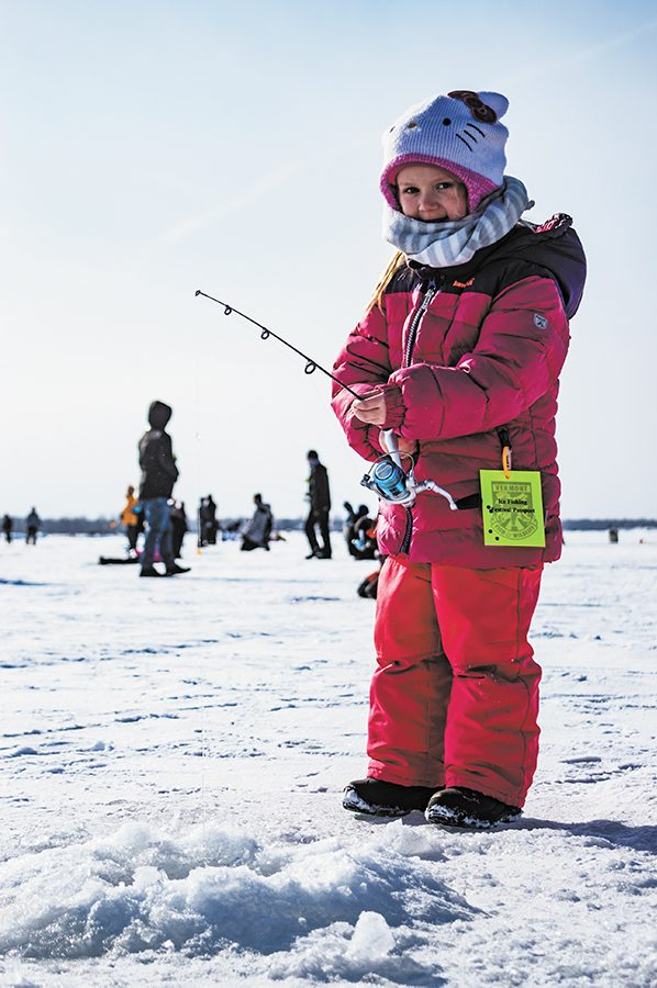 A young angler, kept warm by her Hello Kitty hat and matching pink snow suit, tries for her first catch Jan. 26 at the Free Ice Fishing Day Festival. Student volunteers from the UVM Wildlife and Fisheries Society were there to help hand out fishing equipment and teach the beginners how to ice fish.