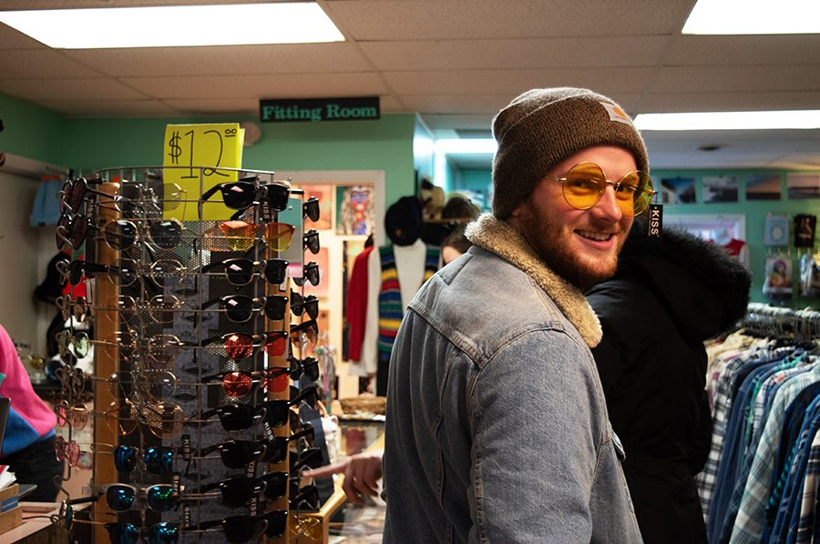 Sophomore Jonathan Barte tries on a pair of $12 sunglasses at Downtown Threads, located in the heart of Church Street. Downtown Threads is unique in that you have the option to fill a bag with clothes from a trunk for $5.
