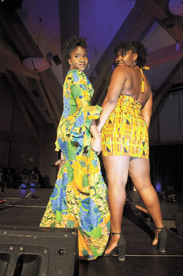 Senior DaneiI Whyte and participant Tristen Thompson hold hands and look back at the audience at the end of the runway in colorful dresses.