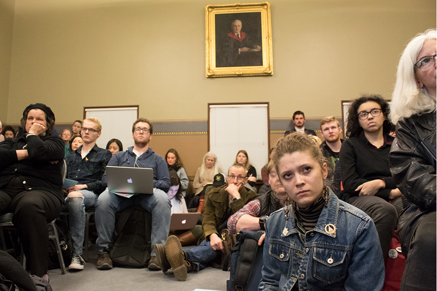 Sophomore Nina Singleton-Spencer sits among students and faculty during the discussion portion of a Feb. 5 United Academics meeting. Students have expressed their frustrations over the College of Arts and Sciences budget changes through posters, memes and protests.