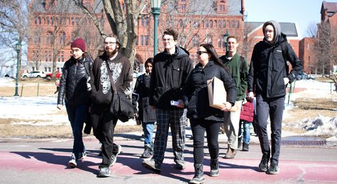 United Academics President Sarah Alexander, associate professor of English,  leads a group of protestors across South Prospect Street into the Waterman building to deliver their petition.