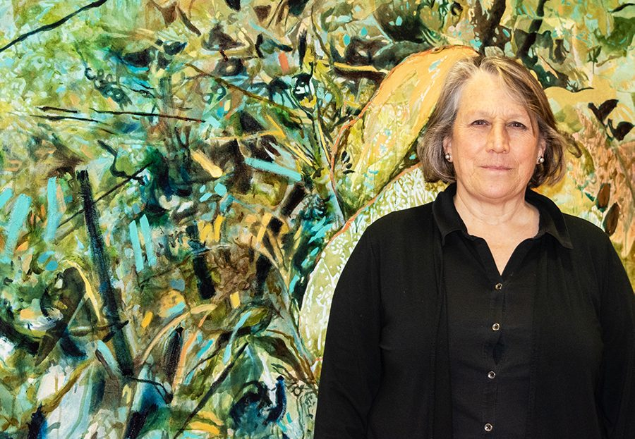 """Senior lecturer of art and art history Cameron Davis stands in front of one of her pieces March 28 in the UVM Medical Center. Her collection is entitled """"Endless Spring"""" which the refers to one of many Buddhist terms for enlightenment or awakening."""