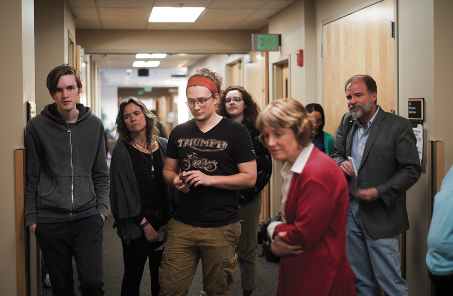 Protesters, including junior Alexander Smith and English professor Nancy Welch, listen to senior Scarlett Moore recount the events of the trial April 4.