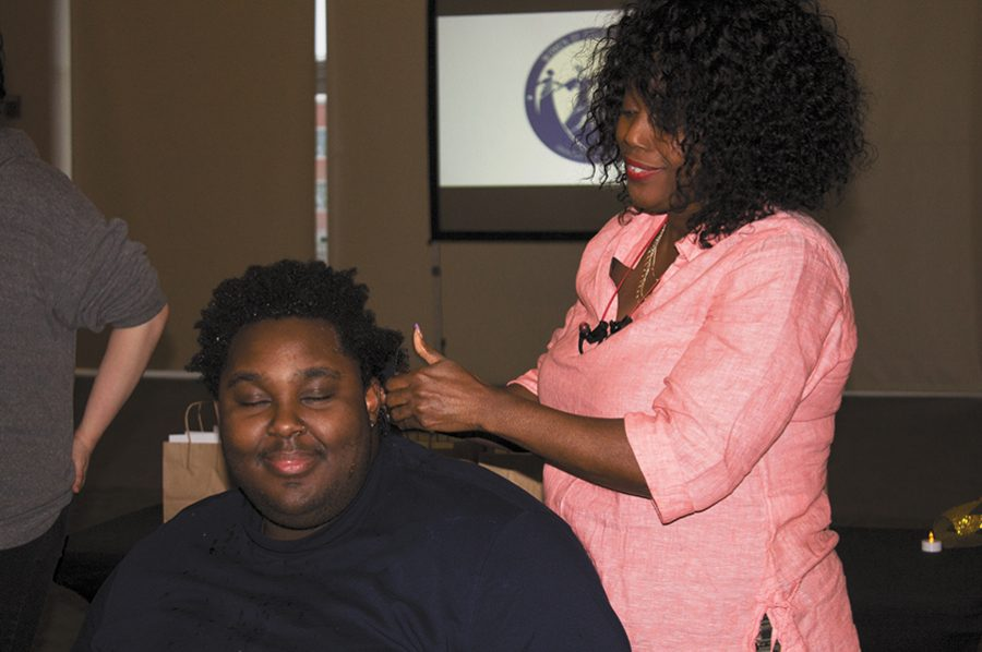Senior Jamal Davis Neal Jr. gets his hair oiled by a stylist from Diversity Hair Salon at the Natural Hair Exposition April 5 in the Silver Maple Ballroom. The event, called Thank God We're Natural, was organized by the Womyn of Color Coalition and the UVM Women's Center.