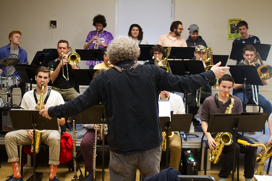Professor of music Alexander Stewart raises his hands to conduct the band into a loud fanfare of sound at a rehearsal for ZappaFest April 11. The band, who has been rehearsing throughout the semester, will be performing Frank Zappa compositions adapted for a jazz ensemble 7:30 p.m. April 20 in the Grand Maple Ballroom.