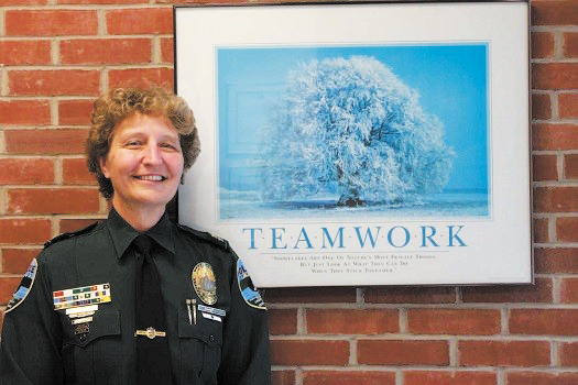 UVM Police Services Chief Lianne Tuomey stands in front of a framed picture that says 'teamwork.' Tuomey went on a leave of absence beginning July 11 and remains on an indefinite paid leave, according to UVM Spokesman Enrique Corredera.