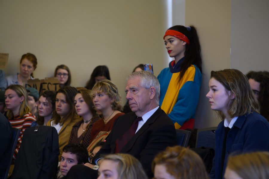 Richard Cate, University treasurer and vice president for finance, sits among over 50 student protesters at a board of trustees meeting, Oct. 26. Despite the protest, the board made no indication that UVM would divest from fossil fuels.
