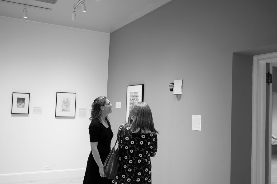 Student curators Meagan Cummins, a senior (Left), and Maud Mayer, a first-year graduate student (Right), admire a work on display in Fleming Museum, Sept. 27.