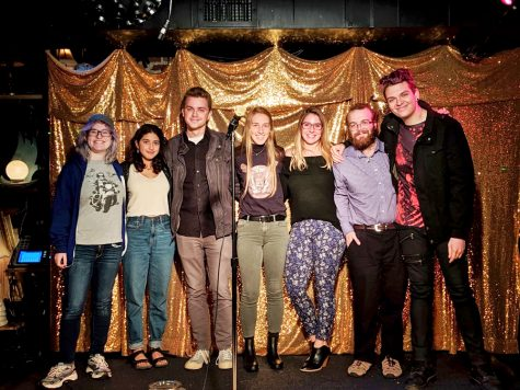 Image Courtesy of The Gist (Left to Right): Senior Lauren Sky, Senior Sunny Nagpaul, Junior Aiden Blasi, Junior Alicia Tebeau-Sherry, Senior Keana Moreau, Senior Chris Soychak and Senior Seth Wade pose on stage at the Light Club Lamp Shop, Oct. 14.