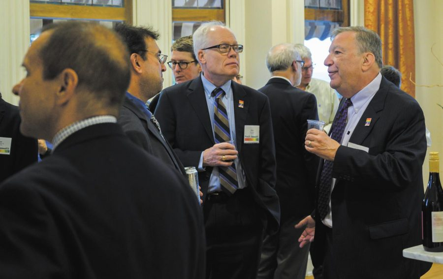 Planning Committee member Sanford Friedman '73 and his partner Jerry Hipps converse with other attendees of the Prism Center's 20th anniversary celebration, Oct. 4. For the first time, the celebration, which took place in the Alumni House, was fully funded by the University.