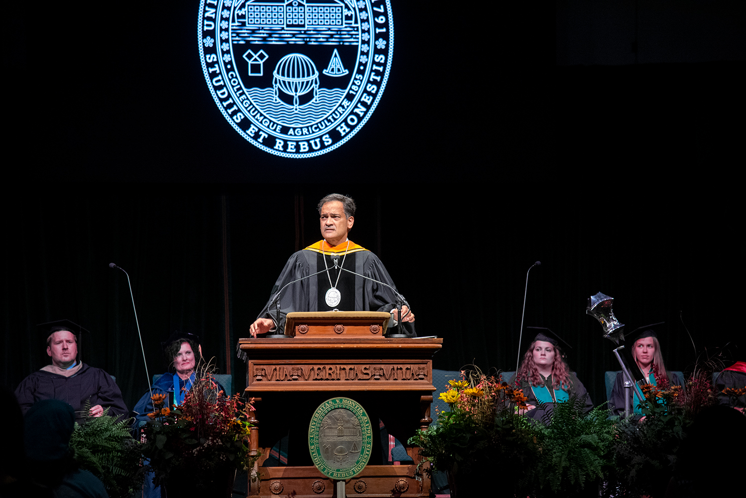 President Suresh Garimella speaks at convocation, Aug. 25. The University seal hangs on the podium and is projected on the curtain behind him.