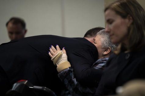 Douglas Kilburn's son, Tyler (left), and widow, Sherry (right) embrace after Tyler made a statement to the press Nov. 8. Tyler asked the public to remember his father was more than just a few seconds of body camera footage.