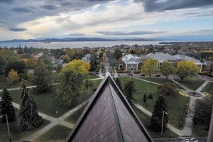 Cars drive on College Street as Lake Champlain reflects the last rays of the sun, all seen from the belfry of Old Mill, Oct. 24. The journey up to the top of the building starts with a locked door, and after many steps, ends with walking up through the floor of the belfry.