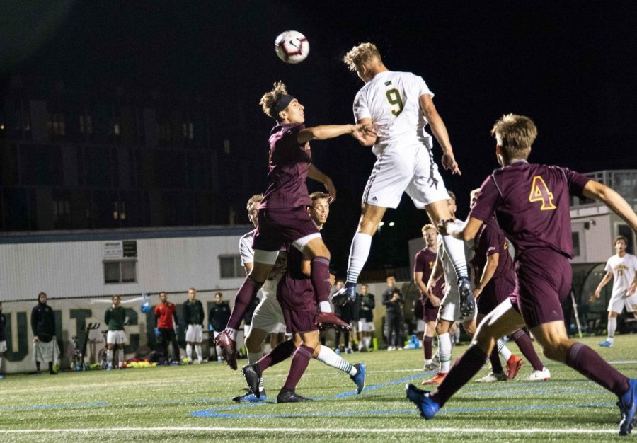 Men's soccer forward Rasmus Tobinski, a first-year, heads the ball over the head of an Iona College player in a September 2019 game.