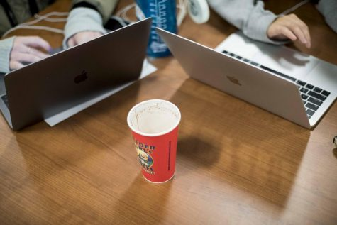 Students study with an empty coffee cup between them at 10:30 p.m. Nov. 19, in Howe Library.