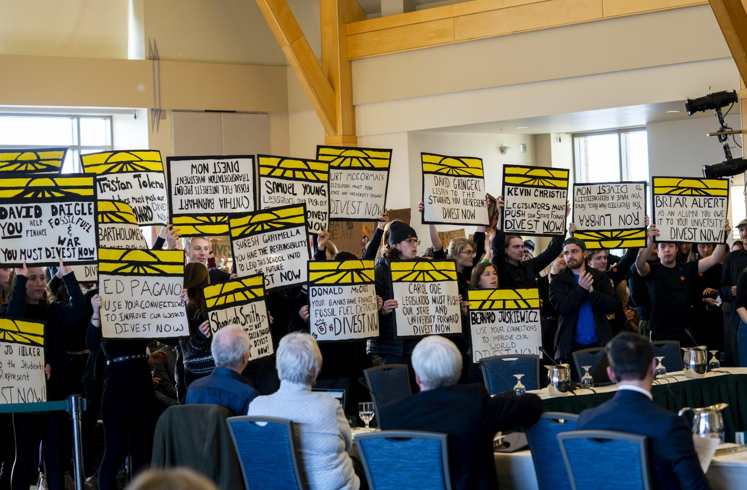 Student protesters hold hand-painted signs following the end of public comment. The group then began to sing,