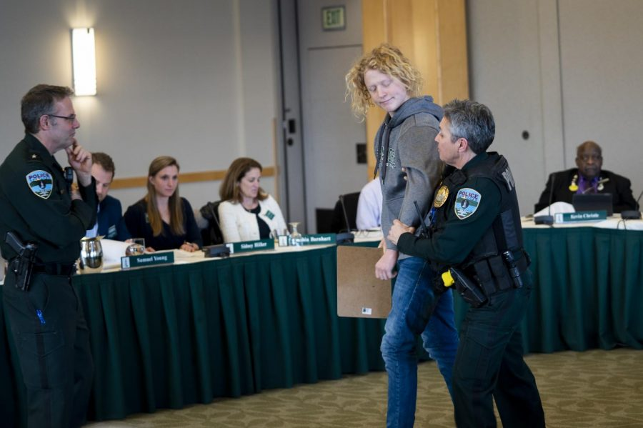 First-year Sam Peck is escorted out of the room by a UVM Police officer while Tim Bilodeau, UVM chief of police looks on. Peck was removed because he refused to move from his seat in the middle of the trustees.