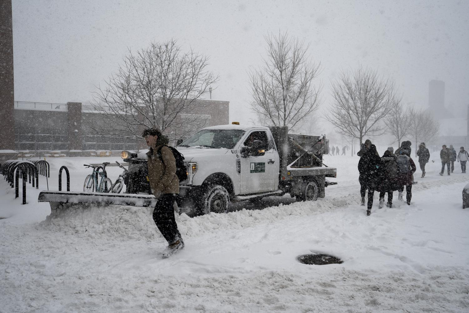 A UVM Physical Plant employee plows snow with a pickup truck as students navigate around him, Feb. 8. UVM's snow removal equipment is housed under the old bleachers at Centennial Field.