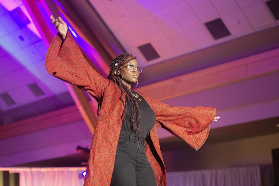 Model and UVM alumna Pam Winee stands with arms stretched wide during the BSU Fashion Show, Feb. 29. The show was hosted by entertainer Jayson Okanlawon.