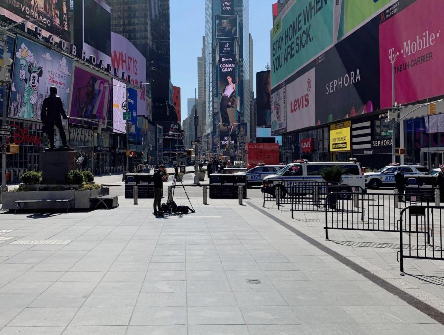 A cameraman stands alone in the streets of Time Square, Mar. 26.