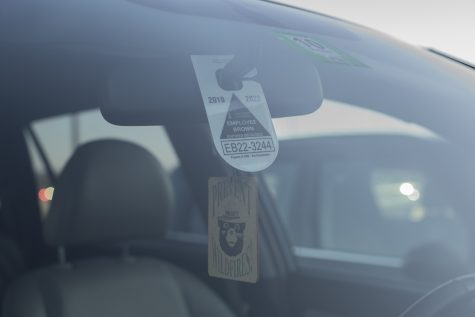 A UVM employee parking pass hangs from the rearview mirror of a car in Jeffords parking lot. Parking permits are assigned according to the workplace of the employee.
