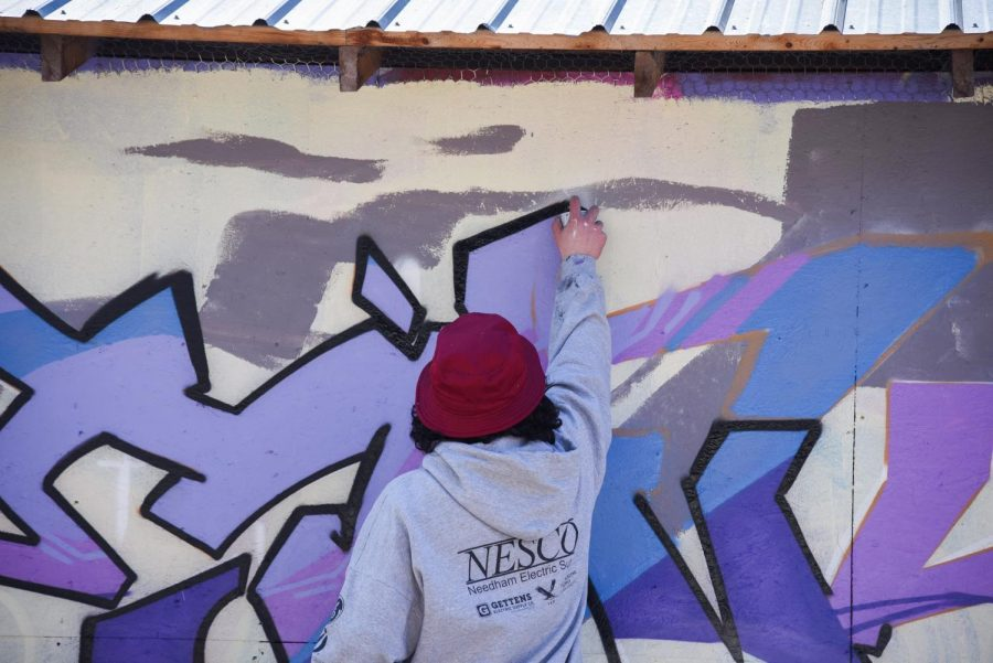 A spray paint artist finalizes his design behind ArtsRiot on the South End.
