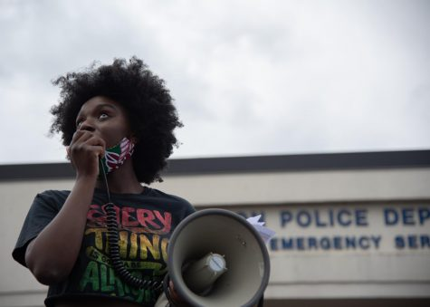 Protest organizer Harmony Edosomwan stands on top of a blue pick-up truck speaking to the crowd with a megaphone at the May 30 protest.