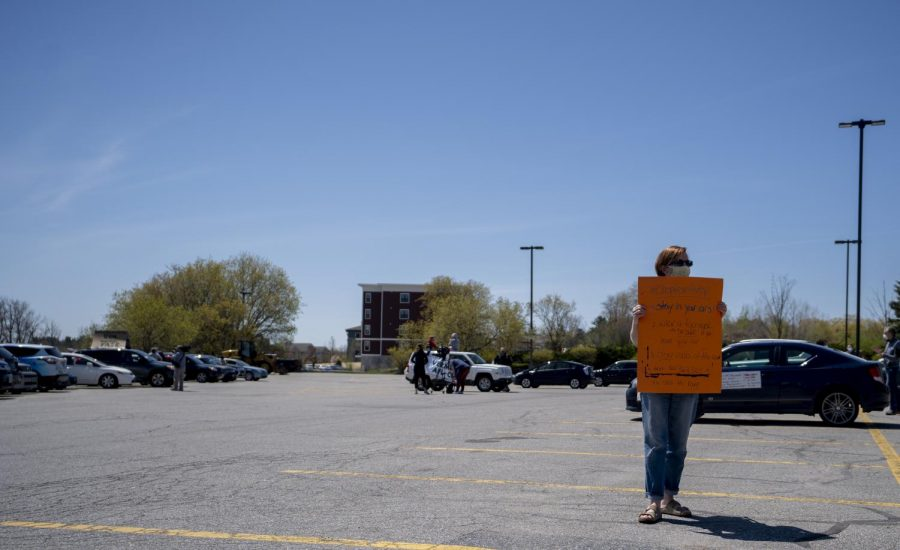 A rally-goer holds a sign in the South Burlington Staple's parking lot with instructions for other protestors gathered May 14, 2020 to rally against looming UVM budget cuts. The sign reads,