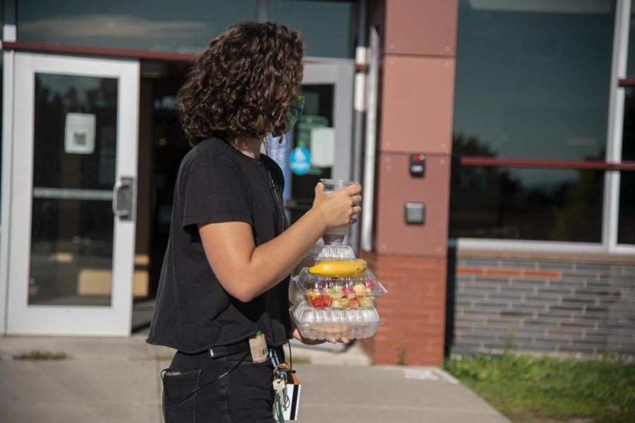 A UVM student in quarantine leaves the dining hall during the breakfast hours with copious amounts of food Aug 20.