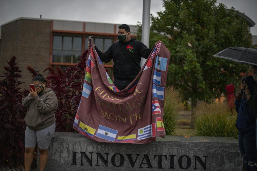 Alianza President Adrian Pastor and former Alianza President Jaylyn Chalco stand in front of the special events flagpole in the pouring rain after removing the Davis Center Flag Sept. 29.