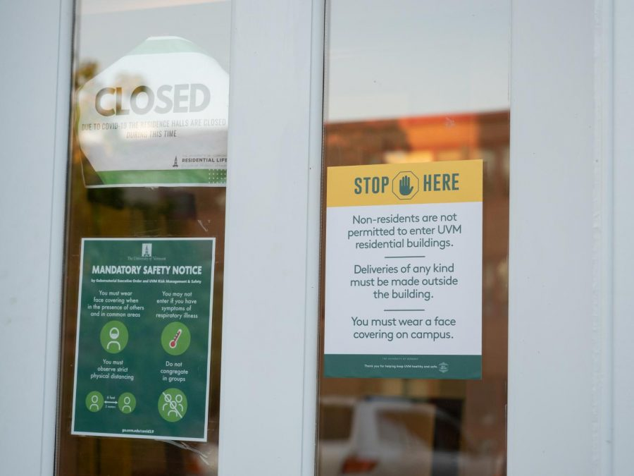 Signage on the door of a UVM residence hall reminds community members of the school's COVID-19 rules, including social distancing and the buildings' new no-guest policy.