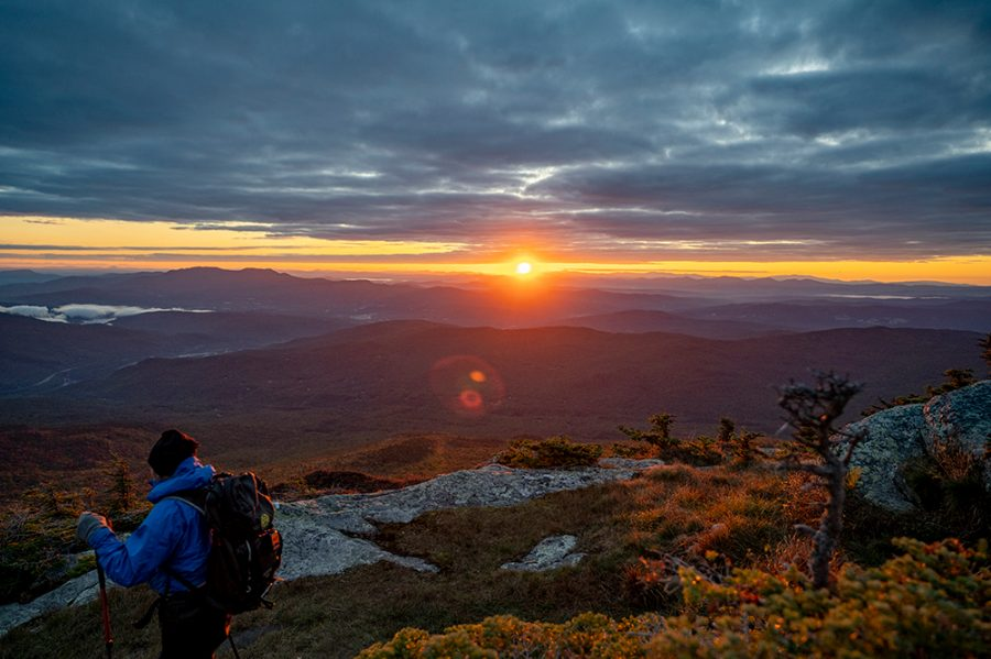 As the sun rises in the eastern sky illuminating the Green Mountains, a hiker begins their descent down from the peak of Camel's Hump Sept. 20.