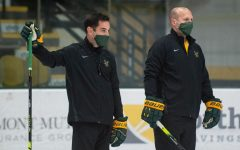 Head Coach Todd Woodcroft stands with Assistant Coach Stephen Wielder on the UVM ice rink holding hockey sticks.
